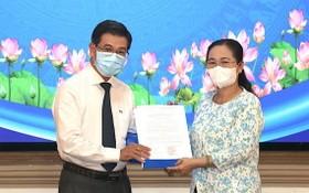阮文勇同志(左)從市人民議會主席阮氏麗手中接過人事委任《決定》。(圖源:雪民)