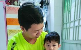 王鍾源抱著患癌症的幼兒家安。