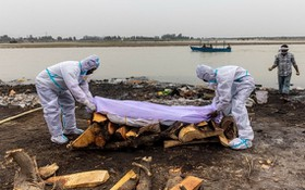 死者親屬在恆河邊準備火化遺體。(圖源:路透社)