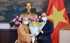 國家主席阮春福(右)接見越南佛教教會理事會理事長釋善仁和尚時贈送鮮花祝賀。(圖源:越通社)