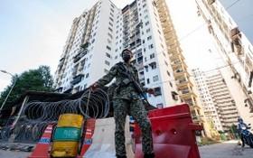 士兵在吉隆坡市郊一處因新冠疫情被封鎖的社區執勤。(圖源:新華社)
