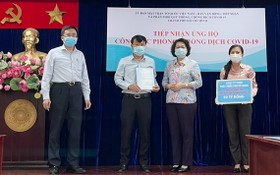 市越南祖國陣線委員會主席蘇氏碧珠(右二)接受富美興發展責任有限公司捐款給購買新冠疫苗防疫基金。