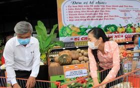 市越南祖國陣線委員會副主席潘嬌清香(右)為市民選購食品。