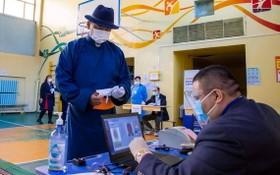 這是6月9日,蒙古人民黨總統候選人呼日勒蘇赫(中)在蒙古國首都烏蘭巴託一處投票站準備投票。(圖源:新華社)