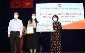 本市市委副書記阮胡海(左)與市越南祖國陣線委員會主席蘇氏碧珠(右)接受萬盛發集團捐助購買疫苗的一萬四千五百億元善款。