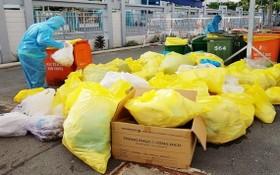 收集和處理醫療廢棄物的工人都穿著防護裝備。