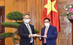 日本大使(左)向政府總理范明政轉交日本首相的通牒。(圖源:VGP)