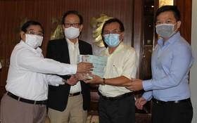 萬盛發集團代表張豐裕(左二)向二府會館理事會和建築公司代表移交最後一期捐款。