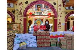 龍華寺住持釋慧功向郡祖國陣線委員會副主席范氏明月轉交救濟物資。