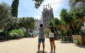 遊客在西班牙巴塞羅那聖家堂附近遊覽拍照。 (圖源:新華社)