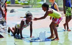 加拿大小童在公園玩水降溫。(圖源:路透社)