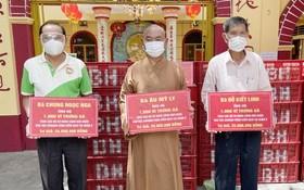 龍華寺護法會副理事長陳健安代表區 美莉、鍾玉娥及杜潔玲3位居士向釋慧功 法師、梅洪峰副主席轉交3000打雞蛋。