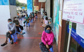 第三郡居民在Co.op Mart超市門外走廊排隊等候購物。(圖源:VnE)
