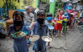 圖為去年4月10日,印尼西爪哇省萬隆市的居民戴著口罩,拿著盤子排隊領取免費食物。 (圖源:路透社)