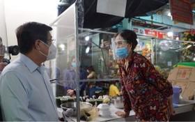 7月18日上午,市人委會主席阮成鋒(左)親往視察第十一郡平泰街市復業情況。(圖源:VNN)