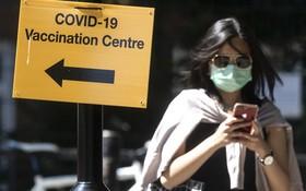 7月16日,行人走過英國倫敦街頭一個疫苗接種點的標誌牌。(圖源:新華社)