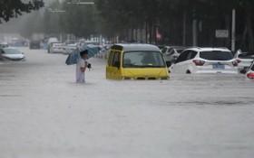 中國河南鄭州強降雨,行人20日涉水通過積水路段。(圖源:互聯網)