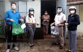 舊邑郡勞動聯團向受疫情影響的自由勞動者贈送必需品。(圖源:越通社)