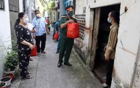市司令部幹部、戰士將援助品帶給貧困勞動者。