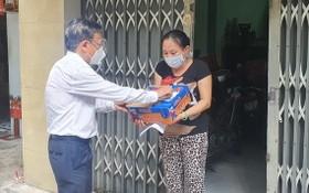 市委民運處主任阮友協向華人貧窮邊緣戶贈送援助品。