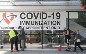 6月18日,人們在加拿大新威斯敏斯特一家新冠疫苗接種中心外排隊等候。(圖源:新華社)
