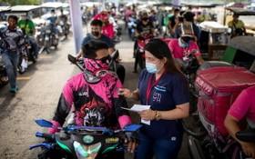 菲律賓15日通報出現首例Lambda變種病毒感染案例。圖為菲國醫護人員向準備接種疫苗的外送員,說明注意事項。(圖源:路透社)