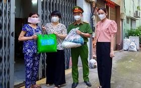 第五郡人委會主席張明嬌(左二)與各代表送援助品給民戶。