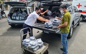 阮維述(左)正在把飯菜搬上車以載到醫院送給病童。
