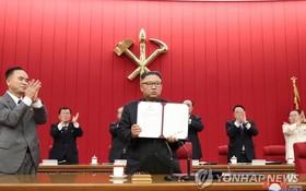 圖為朝鮮勞動黨總書記金正恩出示親自署名的文件。 (圖源:韓聯社/朝中社)