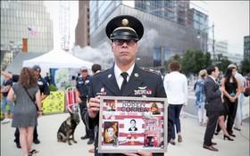圖為二〇一九年在紐約舉行的十八週年紀念,一名出席人士手捧追悼罹難友人的相框。(圖源:路透社)
