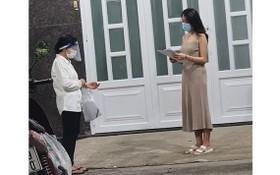 平盛郡第十九坊第三街區第四十六組長黎氏玉貝(左)挨家挨戶派發疫苗接種登記表。