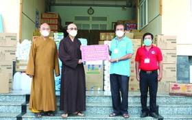 釋通振法師向第八郡祖國陣線委員會副主席梅洪峰轉贈醫療物資及食品。