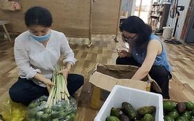 阮氏清翠會長(左)與薇楊會員準備向受疫情影響的貧戶提供食品。