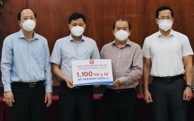 市委副書記阮胡海(左一)、永進公司總經理林松耀(右二)向第十二郡人委會捐贈社會民生必需品。