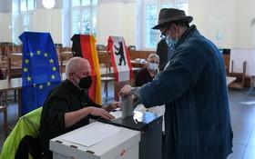 柏林投票站一名選民(右)參加聯邦議院選舉投票。(圖源:新華社)