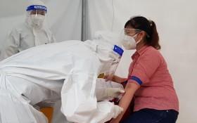 一名女性接受血液取樣以檢測新冠病毒抗體數量。(圖源:何明)