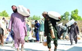 人們在阿富汗坎大哈領取由世界糧食計劃署提供的物資援助。(圖源:新華社)