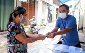 一名受疫情影響的當地居民正領取輔助金。(圖源:互聯網)