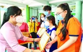 郡婦女會主席陳氏雪幸(左)向貧困優秀生頒發阮氏明開助學金。
