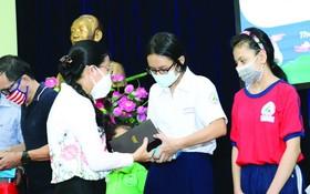 市祖國陣線委員會副主席潘嬌清香向占婆族貧困學生贈送平面電腦設備。