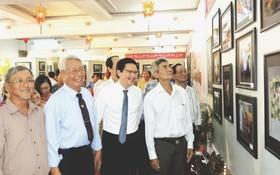 陳傑魯(左二)向各貴賓介紹攝影展。(圖片來源:仁建)