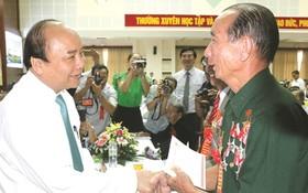 阮春福總理問候對革命有功者。(圖片來源:互聯網)