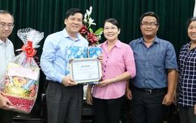 本報主編阮玉英(左二) 和范興主任接受代表團贈送禮物和感謝書。