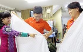 吳氏雲(左)指引新員工檢查產品質量。