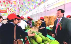 陳榮森(右)向中國消費者推介越南水果。