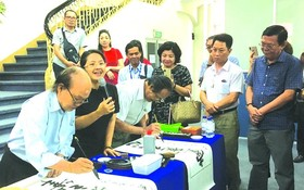 華人書畫家張路與李松年在寫書法作品。