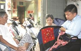 """黃達銘老夫婦向麒麟(右一)贈送距今70多年其母親用於背著弟妹來越的""""咩帶""""。"""