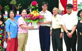 啟秀華文中心校委、老師和學生送花向亞洲餅家 及高慧芳小姐(左三)致謝。