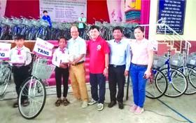 溫陵會館理事與第五郡紅十字會代表贈送 自行車給貧困學生。