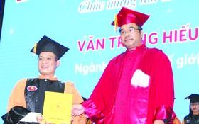 華人幹部文忠孝(左)接受頒發博士學位證書。
